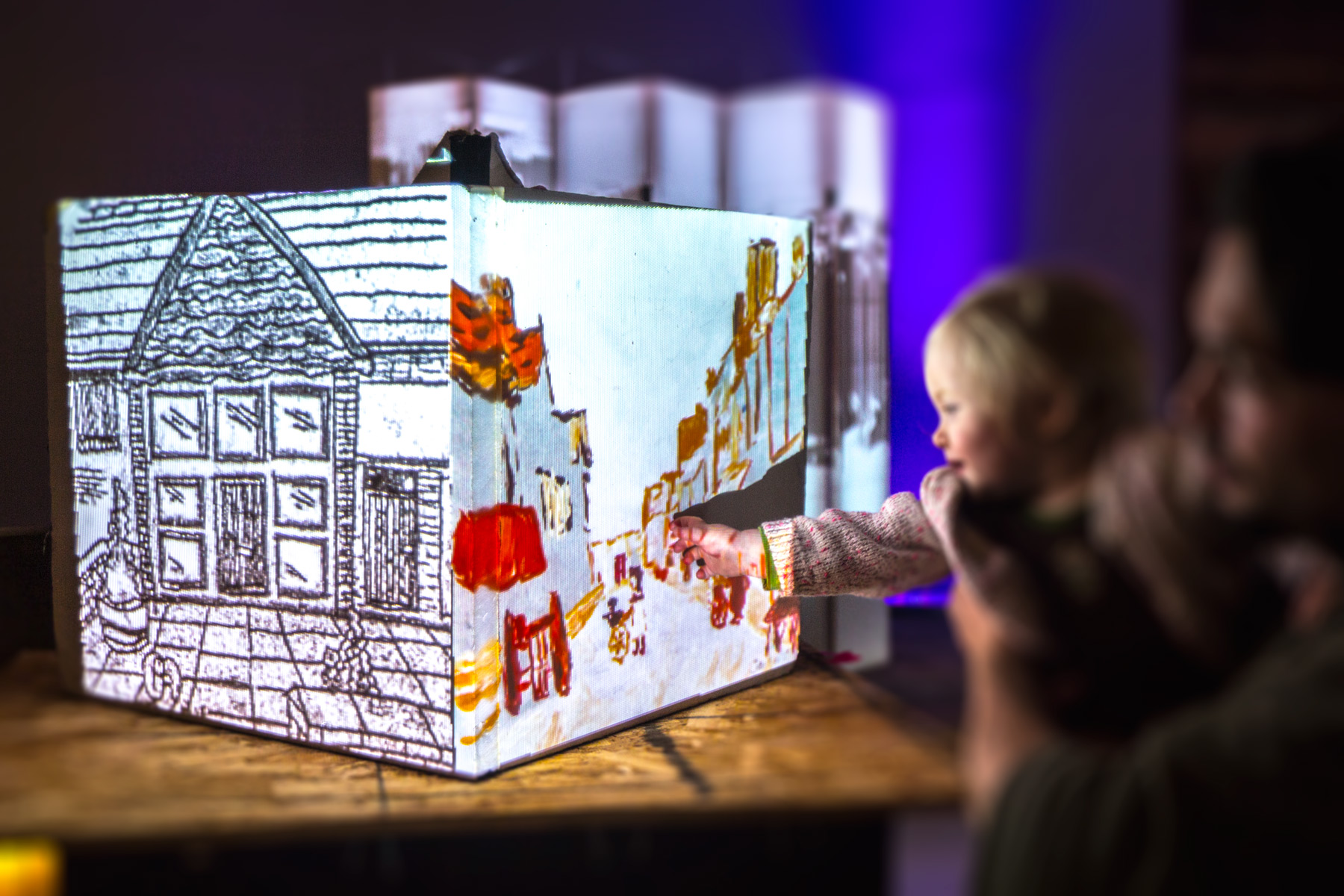 An infant reaches out to a projection mapped cube