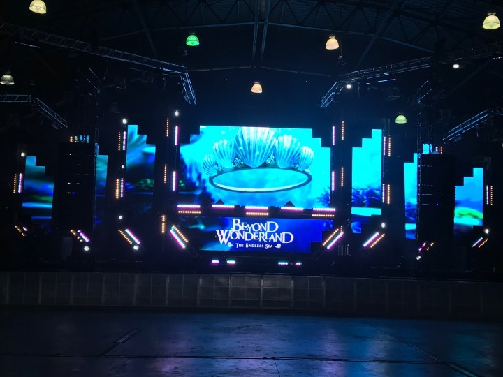 Beyond Wonderland logo and seashells projected on stage in empty concert venue
