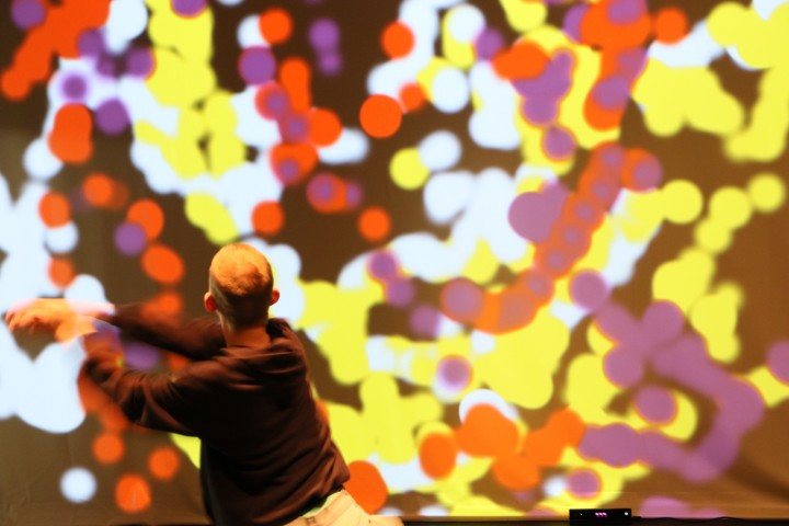 A dancer with his back to the camera extends his arms to the left. In front of him is a projection screen with dots of various colors overlapping and forming trails.