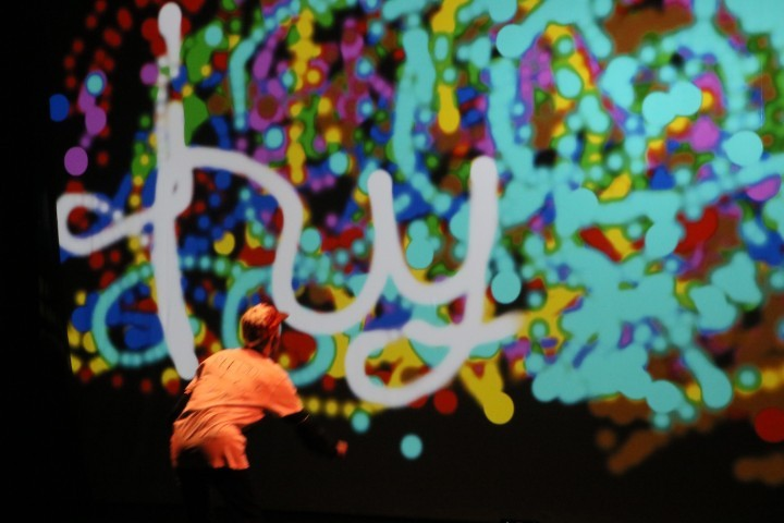 A dancer, bent forward at the waist, faces away from the camera and toward a projection screen, on which he's painting the word 'hyper' in cursive.
