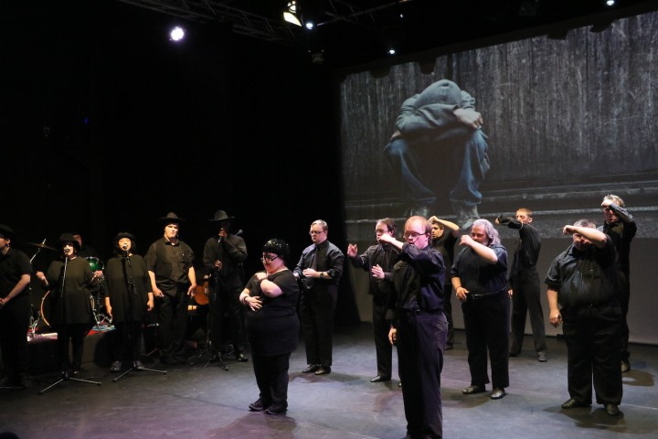 Nine dancers stand in formation making an arm gesture. Several singers with microphones stand in a row off to the side. All are dressed in black. On a projection screen behind the performers is a photo or video of a young person in hoodie and jeans sitting with their head down.