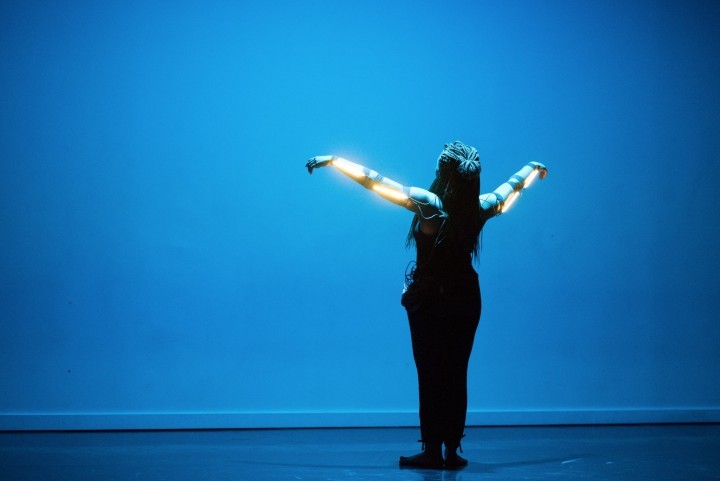 Kendra Ross wearing LED strips on her outstretched arms and facing a wall bathed in blue light