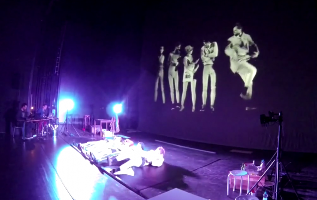 "Video still of the actors and stage in ""The Floor"""